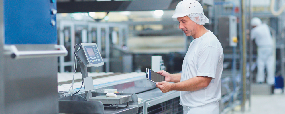 Factory worker standing by a bench scale with a mobile tablet, analysing Overall Equipment Effectiveness data.