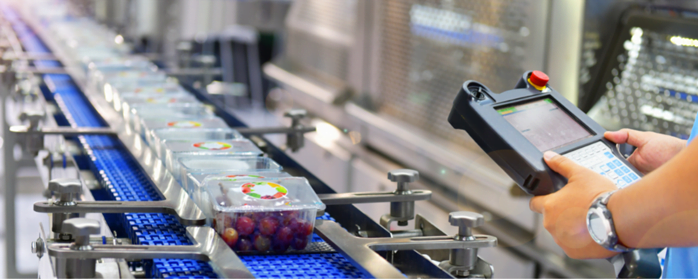 Person monitoring products on conveyor belt with a handheld device enabled by Industrial Internet of Things (IIoT) technologies.