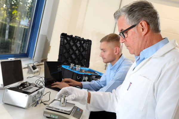 Northern Balance Engineers stood at a work bench calibrating a balance